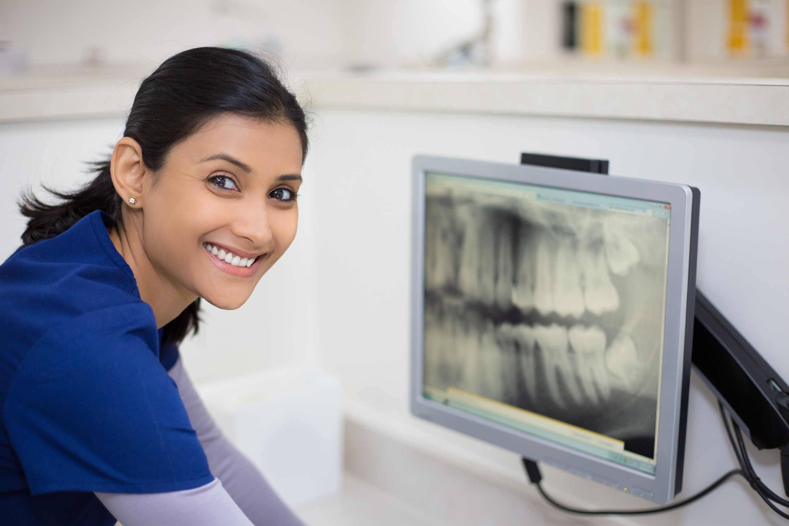 Person smiing at camera while a computer screen is near her showing xrays of teeth for dental jobs school online