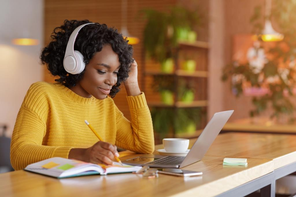 Ultimate Medical Studying - Smiling black girl with wireless headset studying online, using laptop at cafe, taking notes, copy space